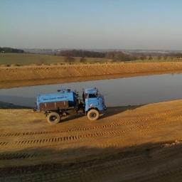 Ein Wasserwagen, der auf einer Baustelle Wasser aus einem Teich holt